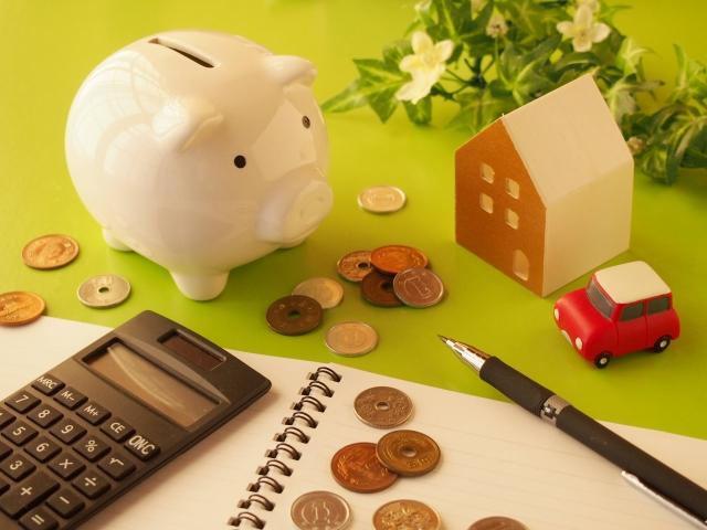 貯金箱と計算機。家計のやりくりについてのイメージ