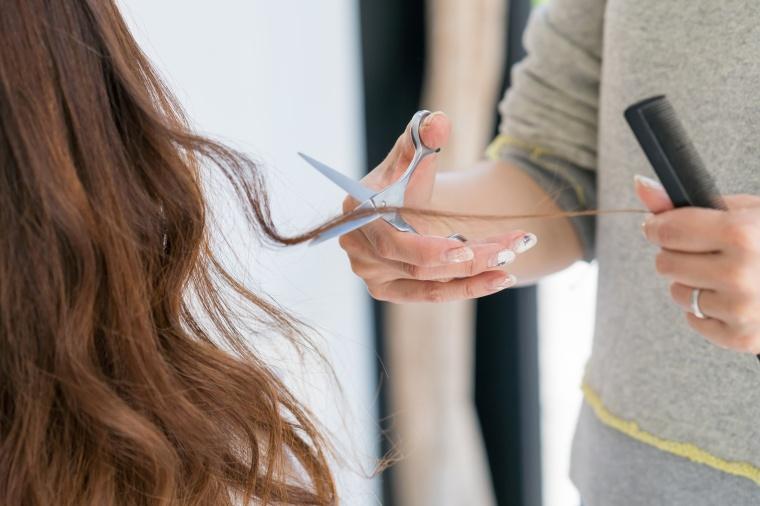 美容院でヘアカットしてもらっている女性