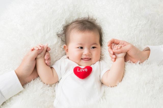 パパママに手を繋がれた可愛い赤ちゃん
