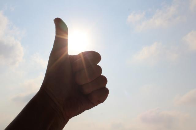 空に親指を立てて、グッドの合図