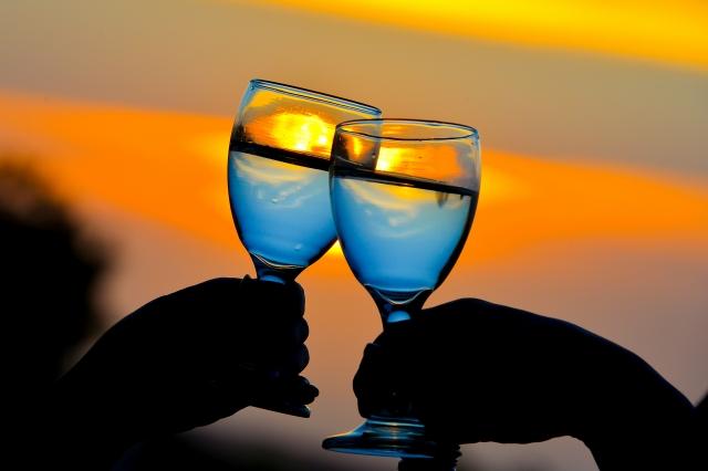 海辺のレストランで乾杯をするカップルの手元と夕焼け