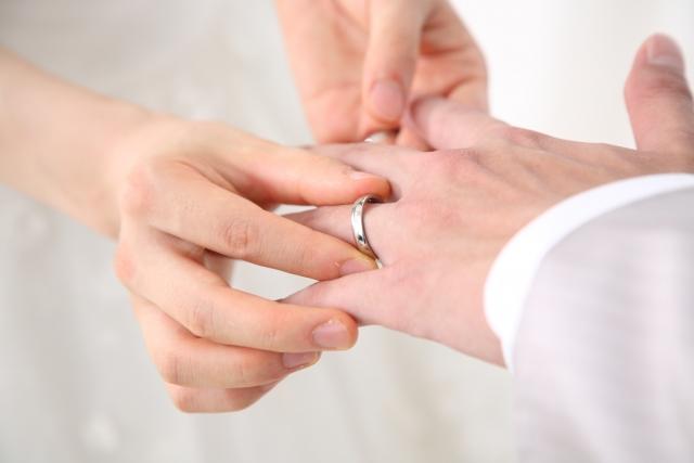 新郎の手に結婚指輪をつける新婦