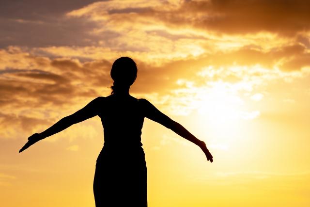 夕陽に向かって手を広げる女性