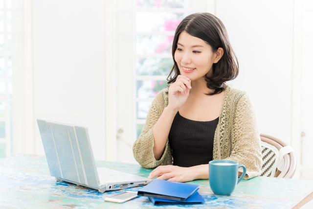 パソコンの前で結婚について考える女性