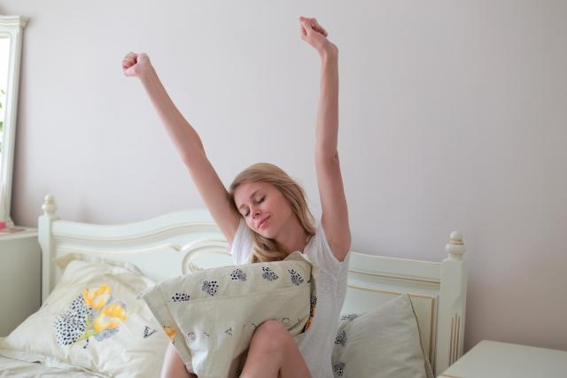 ベッドの上で伸びをする綺麗な女性