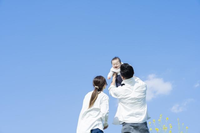 赤ちゃんを高く抱き上げる新婚カップル