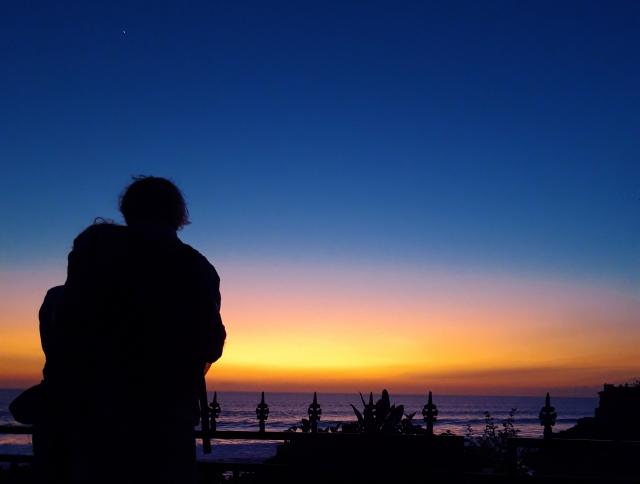 夕暮れの海岸に寄り添うカップル